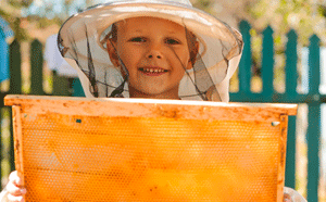 Child with bee hive honey